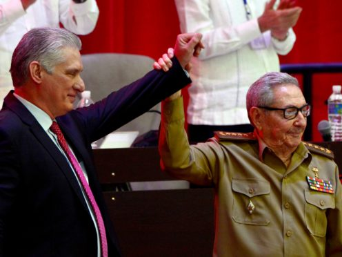 Raul Castro, right, raises the hand of Cuban President Miguel Diaz-Canel after he was elected First Secretary of the Communist Party at the closing session of Cuban Communist Party's 8th Congress at the Convention Palace in Havana, Cuba (Ariel Ley Royero/ACN via AP)