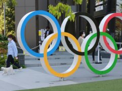 A woman with her dog walks past the Olympic rings in Tokyo (Koji Sasahara/AP)
