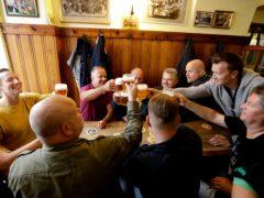 Customers cheer with beer at a pub in Prague, Czech Republic (Petr David Josek/AP)