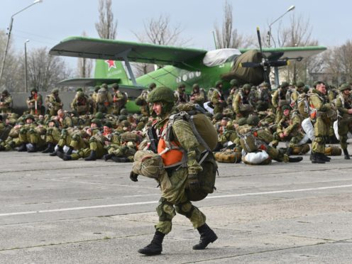 A Russian paratrooper walks as others wait to be loaded into a plane for airborne drills during manoeuvres in Taganrog, Russia (AP)