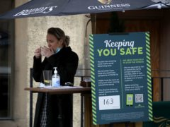 A staff member at the entrance to a pub in the Grassmarket in Edinburgh, as beer gardens, non-essential shops, restaurants and cafes, along with swimming pools, libraries and museums in Scotland reopen today after lockdown restrictions have eased. Picture date: Monday April 26, 2021.