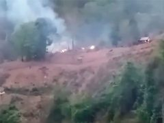 In this image made from video by the Transborder News, smoke rises from a Myanmar Army camp near the border of Myanmar and Thailand Tuesday, April 27, 2021. Ethnic Karen guerrillas said they captured a Myanmar army base Tuesday in what represents a morale-boosting action for those opposing the military's takeover of the country's civilian government in February. (Transborder News via AP)
