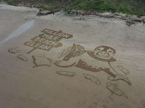 A sand drawing measuring 50 metres has been created on Cayton Bay, Yorkshire, to kick off the million mile beach clean initiative (Surfers Against Sewage/PA)