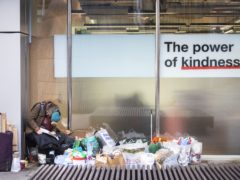 A homeless person sits next to a window in the City of London (Victoria Jones/PA)