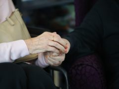 A care home resident and her daughter hold hands during a visit. (Aaron Chown/PA)