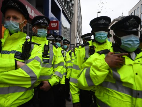 Police officers observe an anti-lockdown protest in London's Oxford Street (PA)