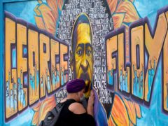A woman pays her respects at a mural at George Floyd Square in Minneapolis on Friday (Julio Cortez/AP)