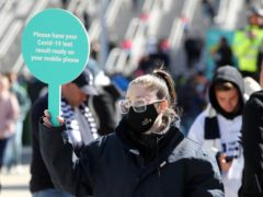 A steward in a mask outside Wembley stadium asks fans for Covid-19 test results (Gareth Fuller/PA)