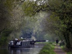 A canal boat travels in the rain along the River Kennet near Theale, Berkshire (PA)