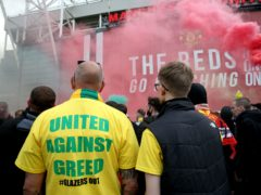 """A fan wears a shirt with a """"United Against Greed"""" message on it (Barrington Coombs/PA)"""