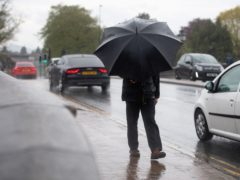 A man holds onto his umbrella in Worcester as wet and windy weather covers much of the region (Jacob King/PA)