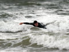 A surfer enjoys the waves in Porthcawl, Wales (Steve Parsons/PA)
