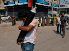 A man carries a refilled oxygen cylinder (Ishant Chauhan/AP)