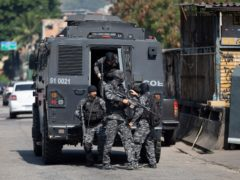 Police get out of an armoured vehicle during an operation against drug traffickers (Silvia Izquierdo/AP)