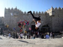 A Palestinian youth performs a back flip at the Damascus Gate to the Old City of Jerusalem as people gather for Eid al-Fitr, marking the end of the Muslim holy month of Ramadan (Mahmoud Illean/AP)