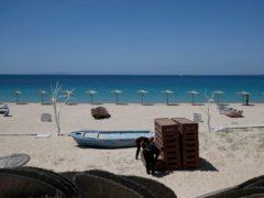 Workers arrange sunbeds as others install umbrellas at Plaka beach on the Aegean island of Naxos, Greece (Thanassis Stavrakis/AP)
