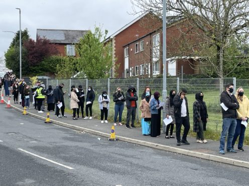 People queue for the vaccination centre at the Essa Academy in Bolton (PA Video/PA)