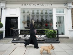 A woman walks past the Amanda Wakeley fashion store in Mayfair, central London, which has gone in to administration (Yui Mok/PA)