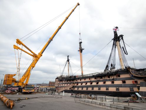 A crane begins the process of removing the main lower mast from HMS Victory (Andrew Matthews/PA)