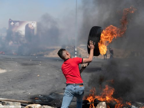 A Palestinian protester rolls a burning tyre towards Israeli army soldiers during clashes at the northern entrance of the West Bank city of Ramallah (Nasser Nasser/AP)