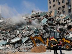 Workers clear the rubble from a building destroyed by an Israeli airstrike on Gaza City (Adel Hana/AP)