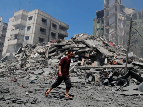 A man walks past the the rubble of the Yazegi residential building that was destroyed by an Israeli airstrike, in Gaza City (Adel Hana/AP)