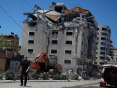 A Palestinian walks by a building hit by an Israeli air strike in Gaza City (Hatem Moussa/AP)