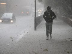 A man walks along the Harrow Road, west London, during as hail storm (Jonathan Brady/PA)