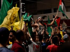 Palestinians dance while celebrating the ceasefire (Adel Hana/AP)