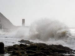 Waves crash below the promenade in Folkestone, Kent (PA)