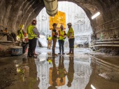 US transport secretary Pete Buttigieg, centre, receives a tour of an underground tunnel for the expansion of the Hartsfield–Jackson Atlanta International Airport plane train tunnel at the Hartsfield–Jackson Atlanta International Airport (Alyssa Pointer/Atlanta Journal-Constitution/AP)