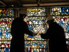 Conservator Matthew Nickels (left) and Master Glazier Tony Cattle, from York Glaziers Trust, remove a stained glass window panel at the start of a five-year, £5m project to conserve York Minster's South East Transept and its medieval St Cuthbert Window (Danny Lawson/PA)