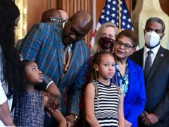 Philonise Floyd, George Floyd's brother, looks down at Gianna Floyd, George Floyd's daughter, while while standing with members of the Floyd family prior to a meeting to mark the anniversary of the death of George Floyd with House Speaker Nancy Pelosi. (Erin Scott/Pool via AP)