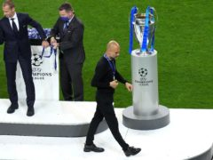 Pep Guardiola is forced to walk past the trophy (Adam Davy/PA)