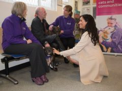 The Duchess of Sussex meets Wully Struthers and his staffies Azzy and Gallis during a visit to animal welfare charity Mayhew (Eddie Mulholland/Daily Telegraph)