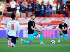 England's Jude Bellingham and Austria's Sasa Kalajdzic take the knee before kick-off (Lindsey Parnaby/PA)