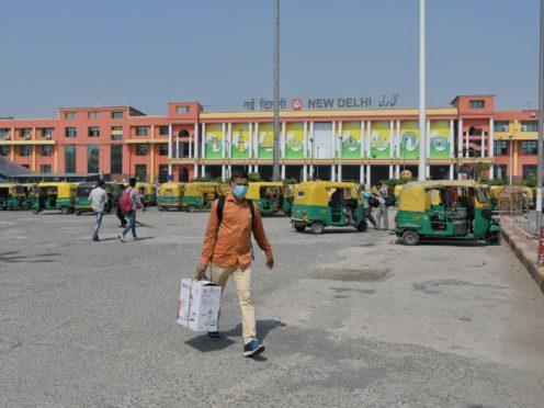 Passengers walk outside the New Delhi railway station in India (Ishant Chauhan/AP)