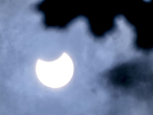 The crescent sun over a cloudy London during a partial solar eclipse (Ian West/PA)
