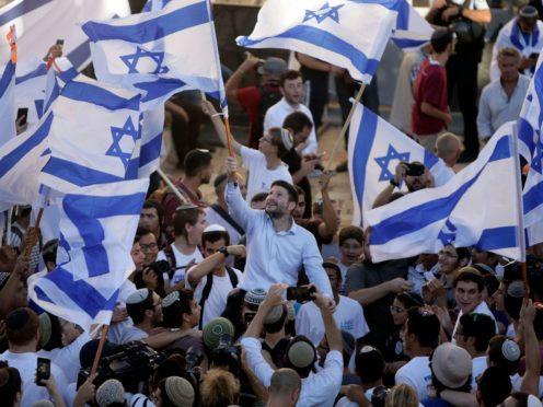 Israeli Knesset member Bezalel Smotrich, centre, waves his country's flag together with other Jewish ultra-nationalists during a march in East Jerusalem on Tuesday, which preceded renewed shelling of Hamas targets by Israel ((Mahmoud Illean/AP)