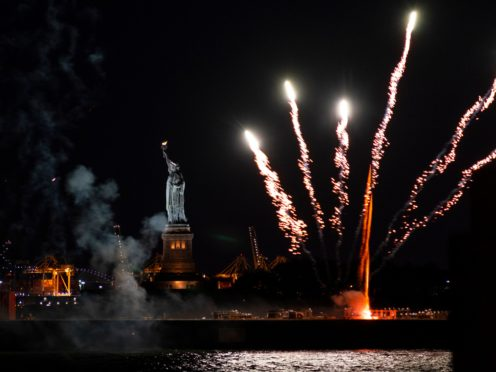 Fireworks launched from a barge explode near the Statue of Liberty in New York Harbour (Craig Ruttle/AP)