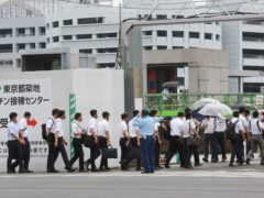 Police officers and firefighters arrive to receive their coronavirus vaccines in Tokyo (Koji Sasahara/AP)