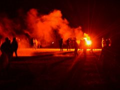 Youths stand in a field during clashes with police (AP)