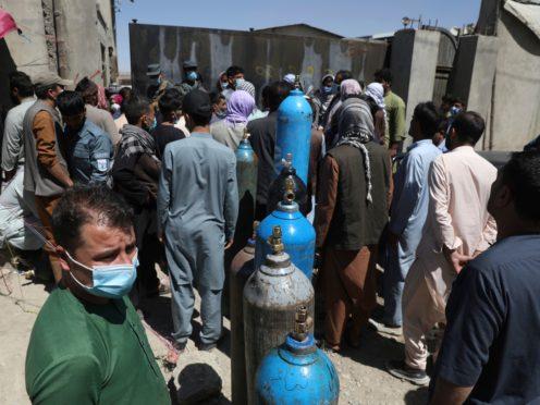 Men wait to get their oxygen cylinders refilled (Rahmat Gul/AP)