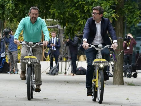 Greater Manchester transport commissioner Chris Boardman (left) and mayor of Greater Manchester Andy Burnham test out the bike hire scheme (Peter Byrne/PA)