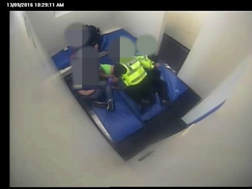 Andrew Hall (on floor in green t-shirt) being restrained by police officers (West Yorkshire Police/PA)
