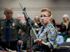 A police detective holds up a Bushmaster AR-15 rifle (Jessica Hill/AP)