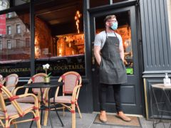 A bartender wearing a face mask stands outside a bar in Cardiff (PA)