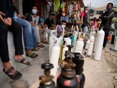 People queue up to refill their oxygen tanks at a filling station in Jakarta, Indonesia (Dita Alangkara/AP)
