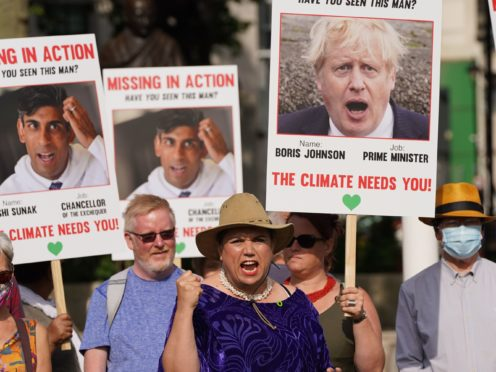 Campaigners hold placards of Prime Minister Boris Johnson and Chancellor Rishi Sunak during a demonstration organised by the Climate Coalition in London's Parliament Square to mark 100 days to go until the Cop26 climate summit in Glasgow (Stefan Rousseau/PA)