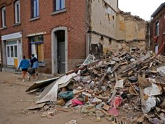 Two girls carry a bucket after dumping household debris in a pile after flooding in Vaux-sous-Chevremont, Belgium (AP)